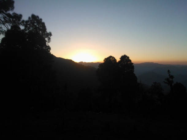 Sun setting behind Himalayan hills covered with Pine and Oak Tree forest, Jhaltola, Pithoragarh, Uttarakhand