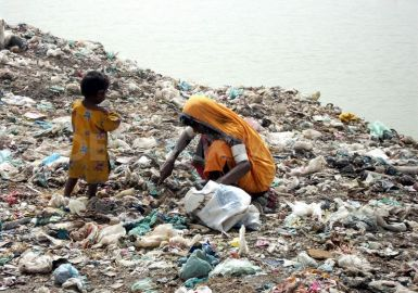 Mother and daughter search in waste dump for food