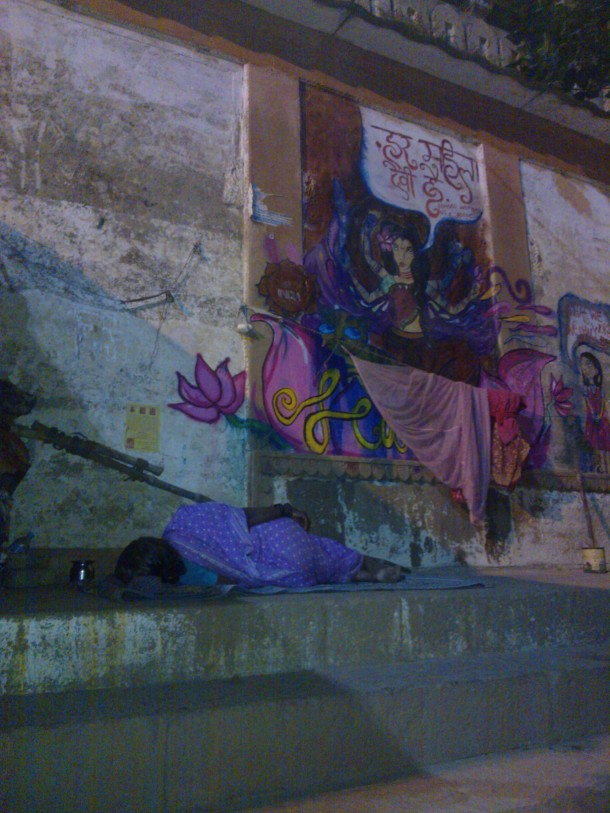 A woman sleeping on the banks of Ganga; under an image which proclaims 'every woman is a goddess'