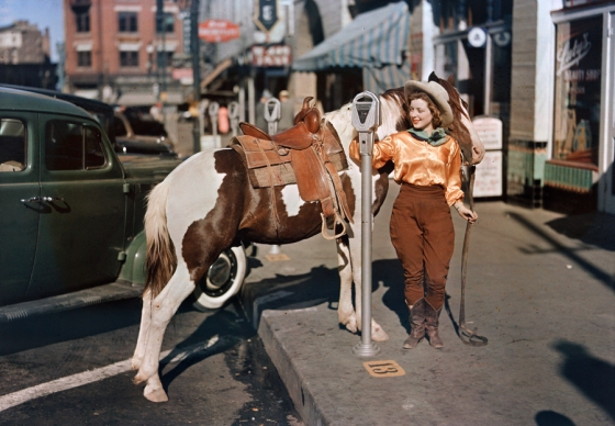 October 1939, USA : A cowgirl puts a nickel in an El Paso parking meter to hitch her pony