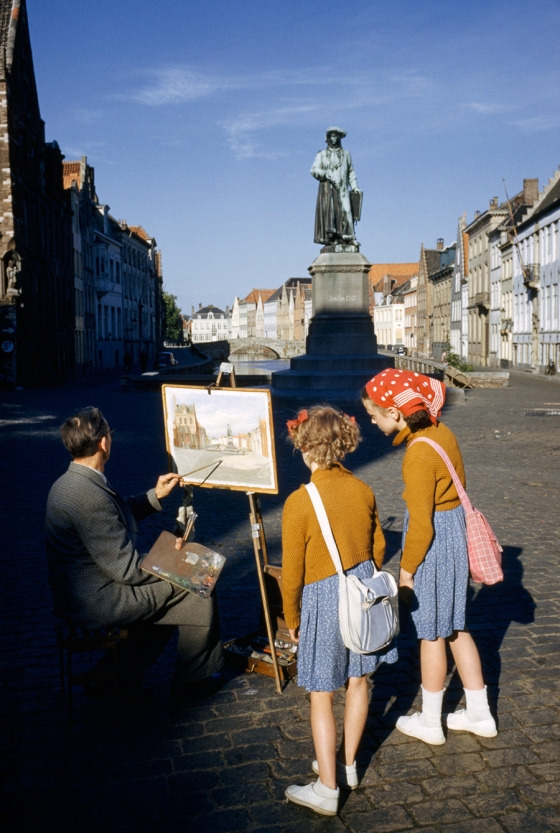 May 1955, Belgium : Girls watch artist painting picture of statue of Flemish artist in Bruges