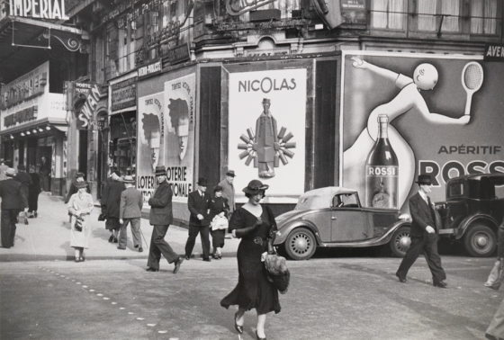 1935, Paris : Parisians walk on the street past lottery and vermouth advertisements