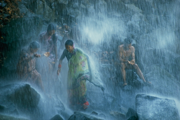 November 1988, Madhya Pradesh, India : Pilgrims bathe in the Narmada's 160-foot-tall Kadil Dhara waterfall in India