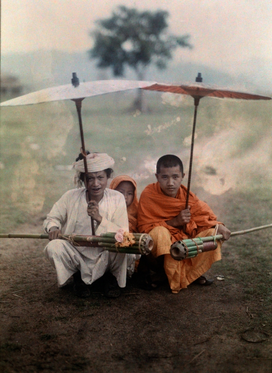 November 1931, Myanmar/Burma : Shan man and two priests prepare to set-off bamboo rockets in rain