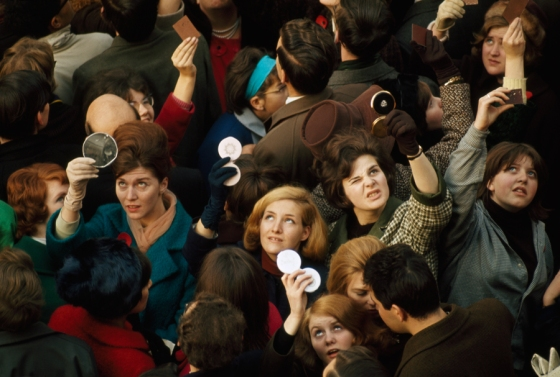 June 1966, London : Women use compact mirrors in packed crowd to catch sight of the queen in London